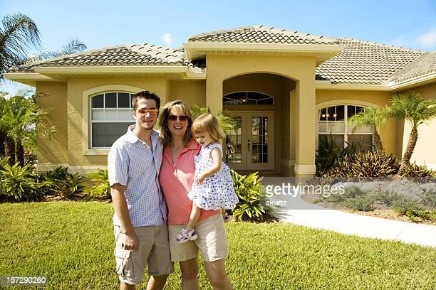 Família feliz na frente de sua nova casa
