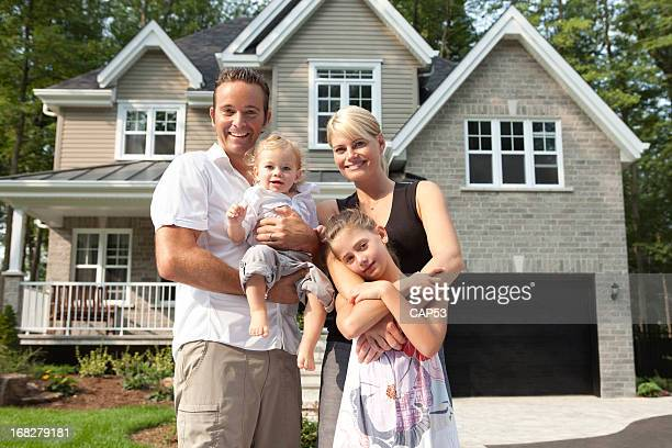 Happy Family In Front Of Their New House