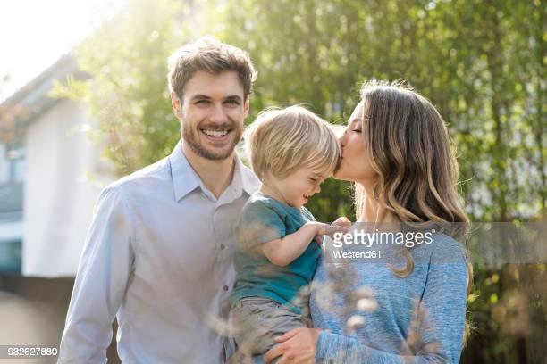 happy family in garden in front of bamboo plants with mother kissing son - familie mit einem kind stock-fotos und bilder