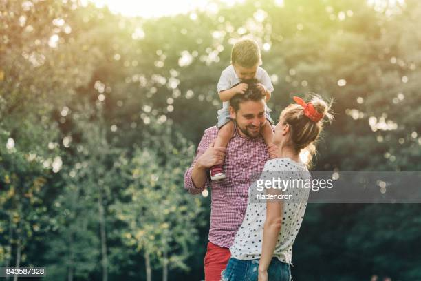 happy family in the park - piggyback stock pictures, royalty-free photos & images