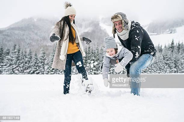 happy family in winter landscape - warm clothing stock pictures, royalty-free photos & images