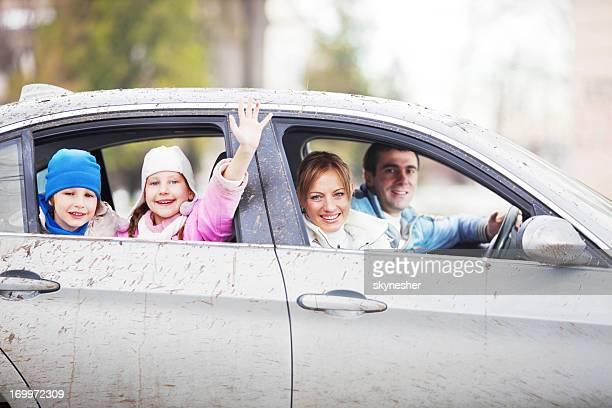 Happy family ina very dirty car.