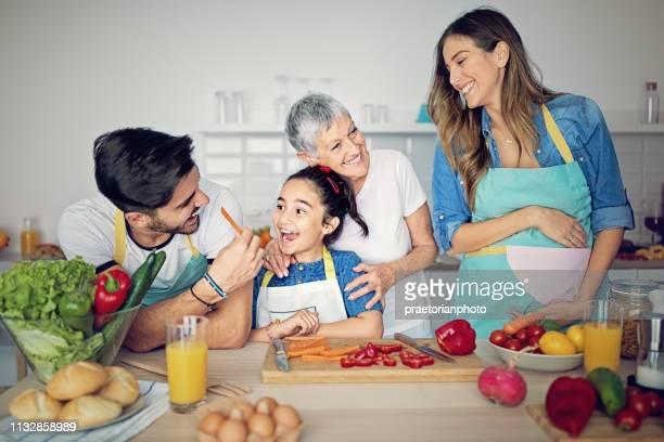 famille heureuse cuisine ensemble dans la cuisine - grossesse humour photos et images de collection