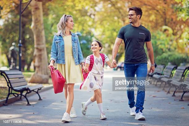 happy family is going to the school together - first day of school stock pictures, royalty-free photos & images