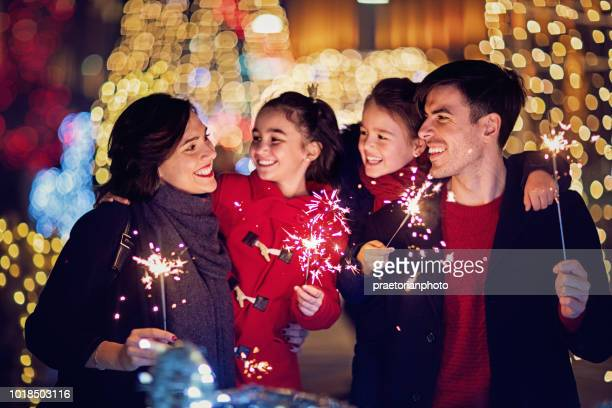 happy family is holding fireworks at christmas - new year stock pictures, royalty-free photos & images