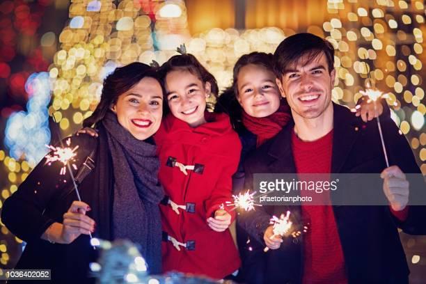 幸せな家族のクリスマスの花火を保持しています。