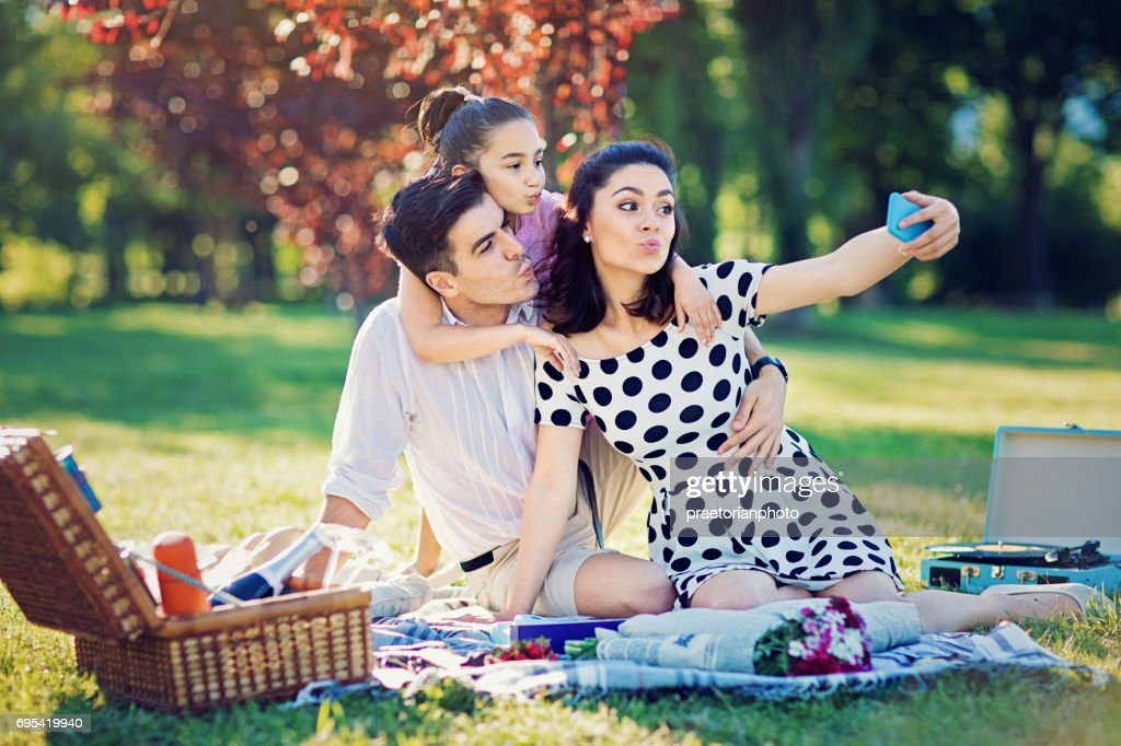 Happy family is making funny duck face and taking selfie at the picnic in the park : Stock Photo
