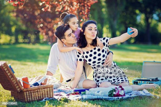 Happy family is making funny duck face and taking selfie at the picnic in the park