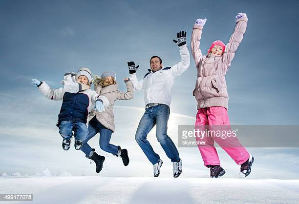 Happy family jumping on snow with arms raised.