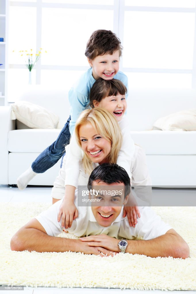 Happy family laying down one the other. : Stock Photo