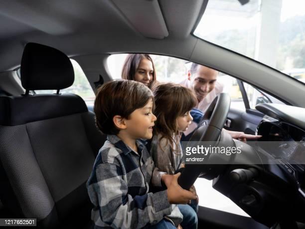 ディーラーで車を見て幸せな家族 - 試運転 ストックフォトと画像