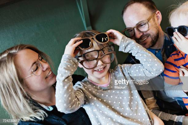 Happy family looking at girl wearing various eyeglasses on face at workshop