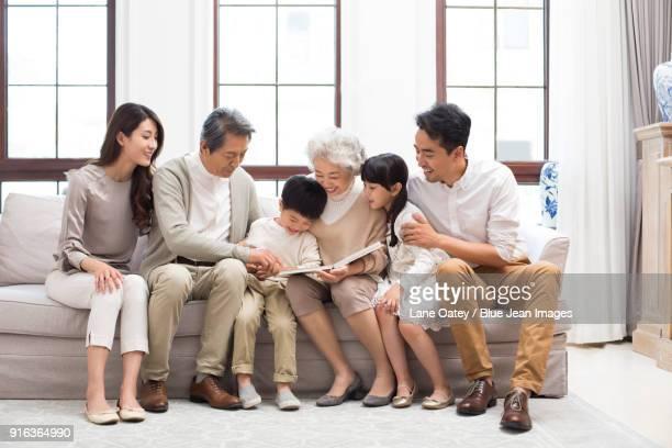 Happy family looking at photo album on sofa