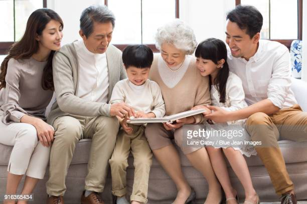 happy family looking at photo album on sofa - asian granny pics stock photos and pictures