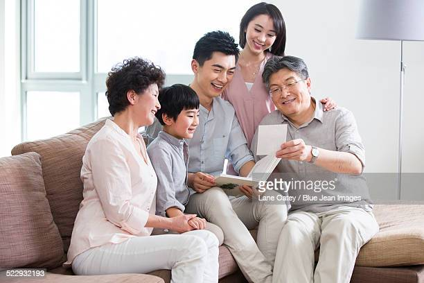 happy family looking at photo album - asian granny pics stock photos and pictures
