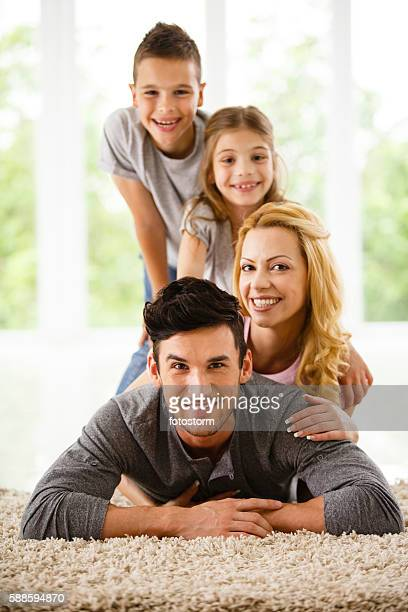 Happy family lying down on the floor at home