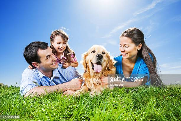 Glückliche Familie liegen im park mit Ihrem Hund.