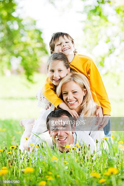 Happy family lying on a pile in park.