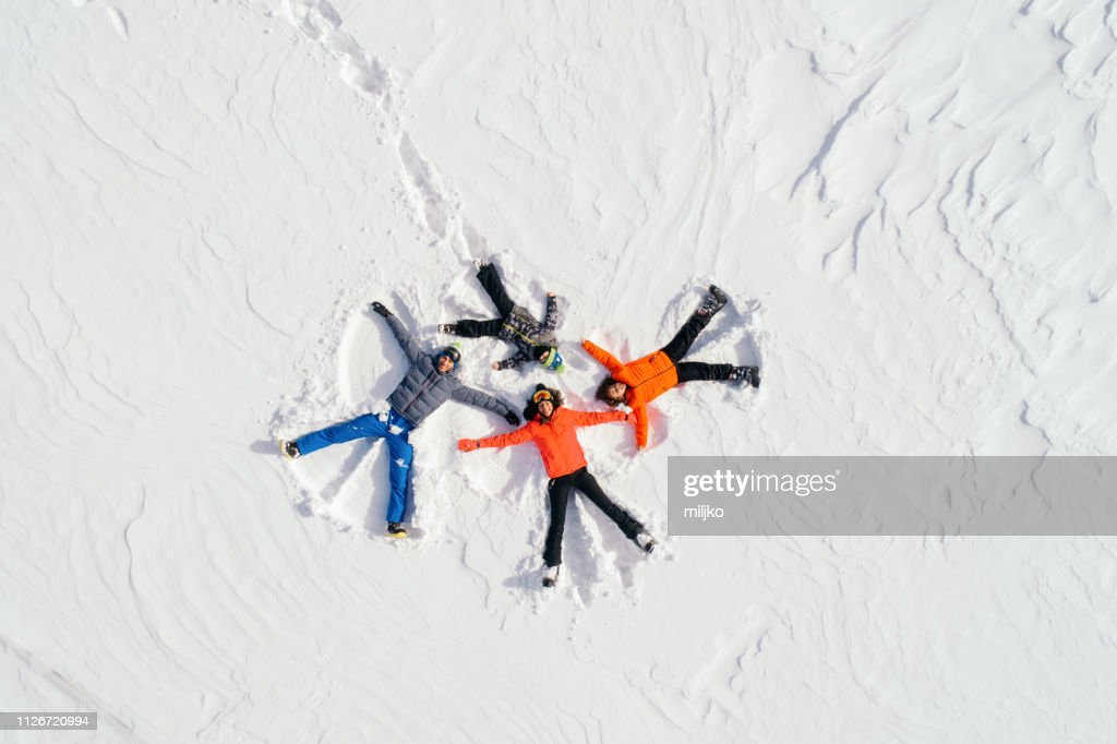 Happy family lying on back on snow : Stock Photo