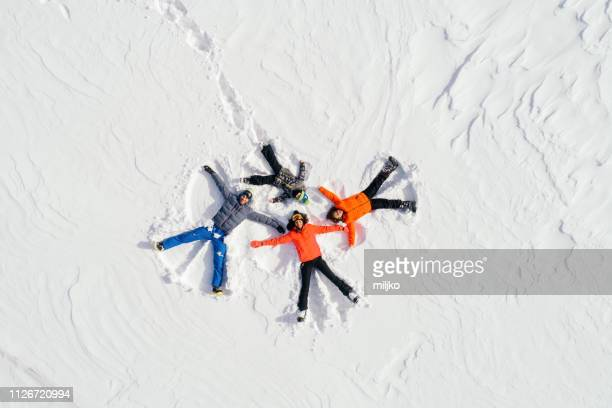 happy family lying on back on snow - snow angel stock photos and pictures