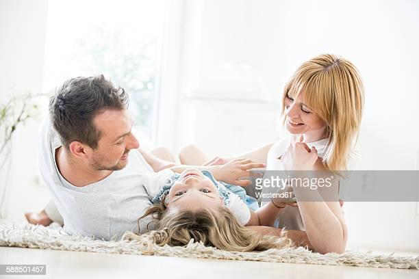 Happy family lying on floor messing around