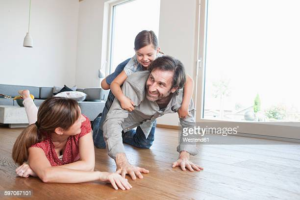 Happy family lying on floor, playing with daughter