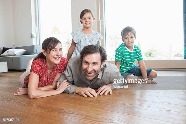 Happy family lying on floor, smiling