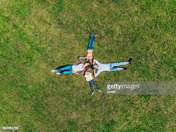 happy family lying on the grass - lying down stock pictures, royalty-free photos & images