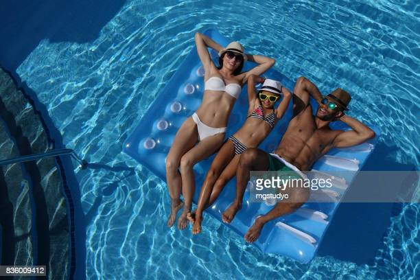 happy family lying to pool raft in swimming pool - girls sunbathing stock pictures, royalty-free photos & images
