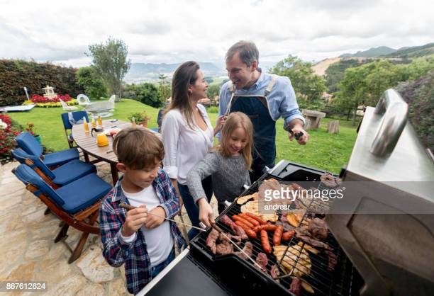 happy family making a barbecue outdoors - small group of people stock pictures, royalty-free photos & images