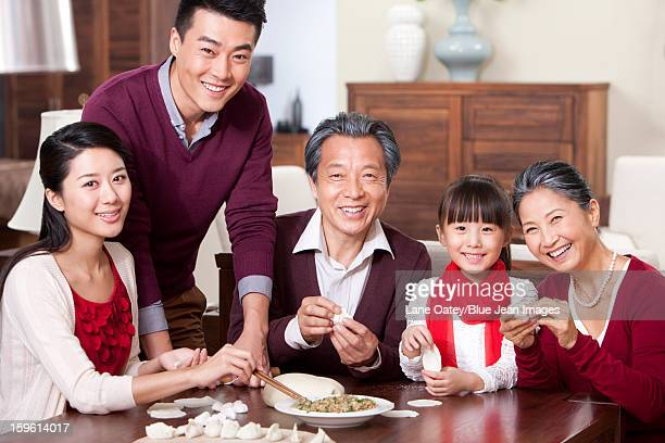 Happy family making Chinese dumplings during Chinese New Year