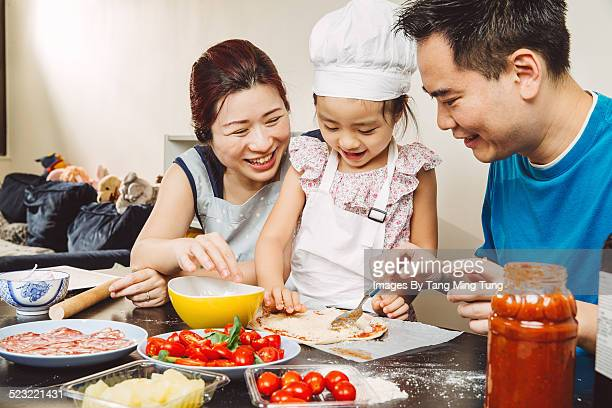Happy family making pizza together joyfully