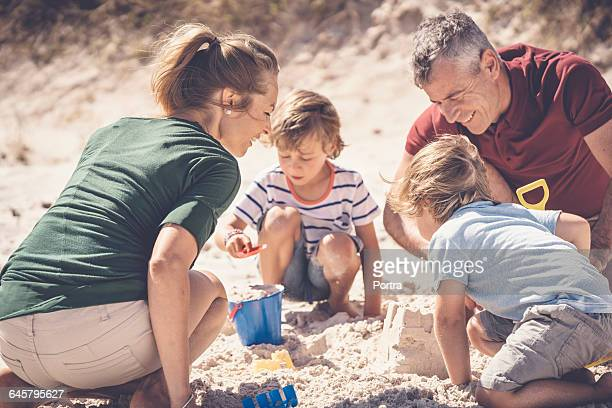 Happy family making sandcastle at beach