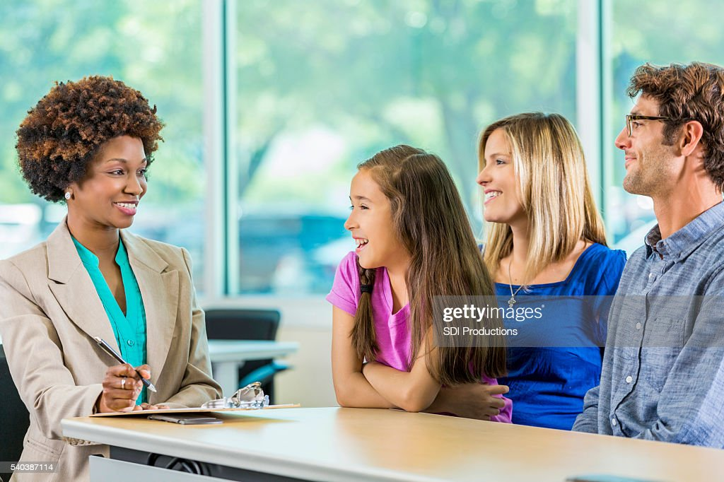 Happy family meeting with African American Teacher : Stock Photo
