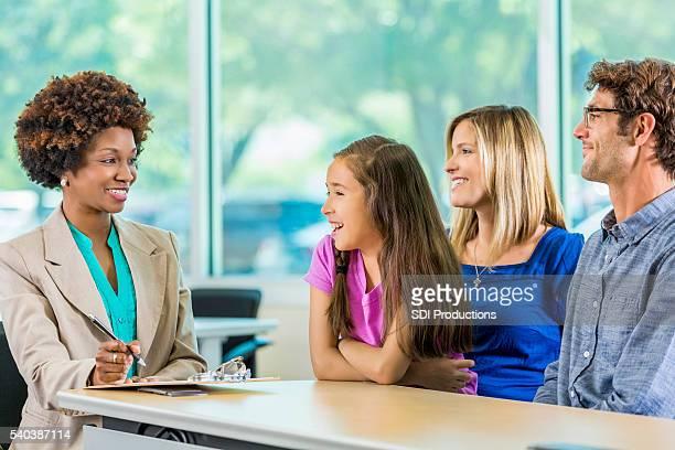 Glückliche Familie treffen mit afrikanische amerikanische Lehrer