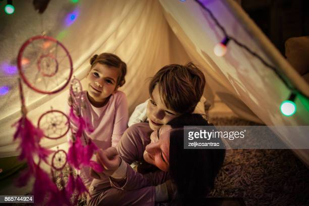 Happy family mother and child reading a book in tent at