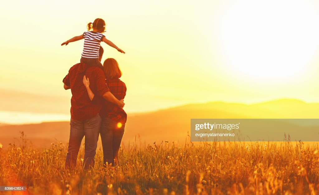 Happy family: mother father and child daughter on sunset : Stock Photo