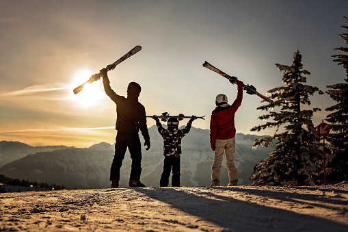 Happy family, mother, father and child, skiing on sunset in austrian Apls, beautiful scenery landscape - gettyimageskorea