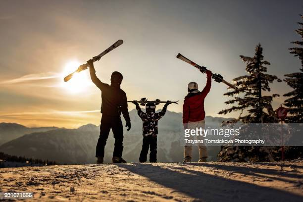 Happy family, mother, father and child, skiing on sunset in austrian Apls, beautiful scenery landscape