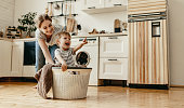 Happy family mother housewife and child   in laundry with washing machine