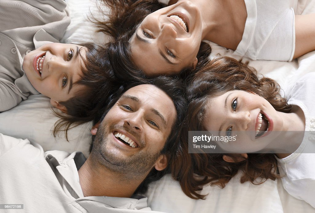 Happy family of 4 smiling at camera : Stock Photo