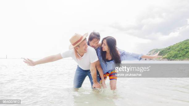 happy family of father, mother and daughter on the beach
