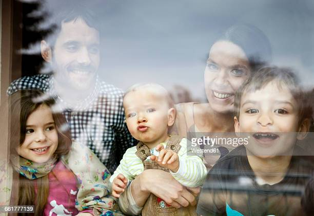 happy family of five looking through window pane - 30 39 años fotografías e imágenes de stock