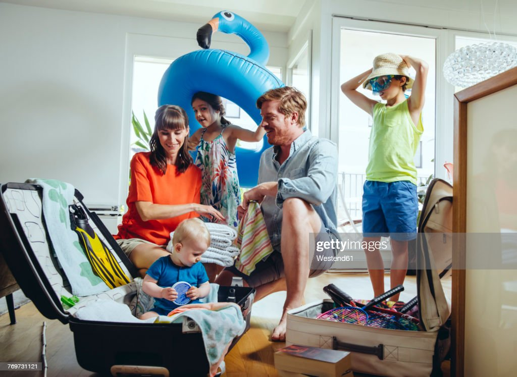 Happy family of five packing for holiday trip : Stock Photo