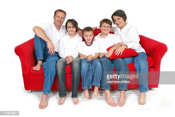 Heureuse famille de cinq assis sur un canapé rouge gros