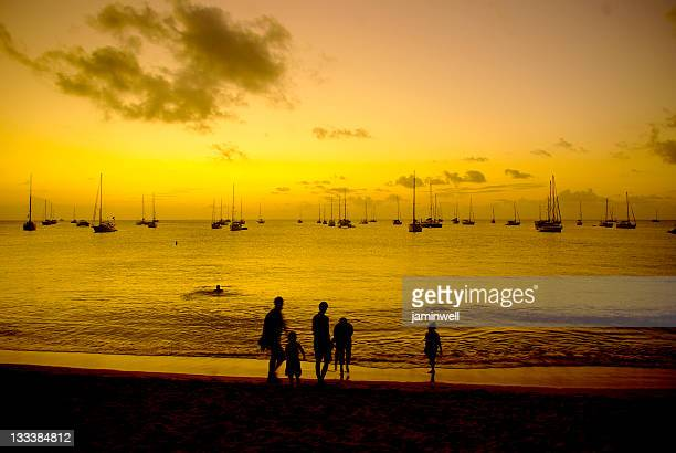 happy family of five vacationing on beach at sunset