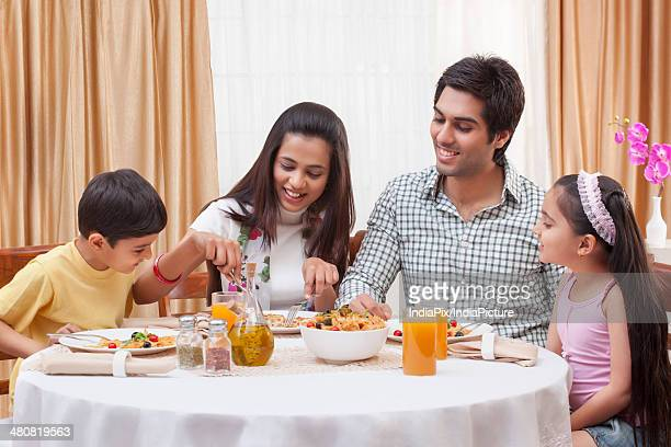 Happy family of four having food together at restaurant table