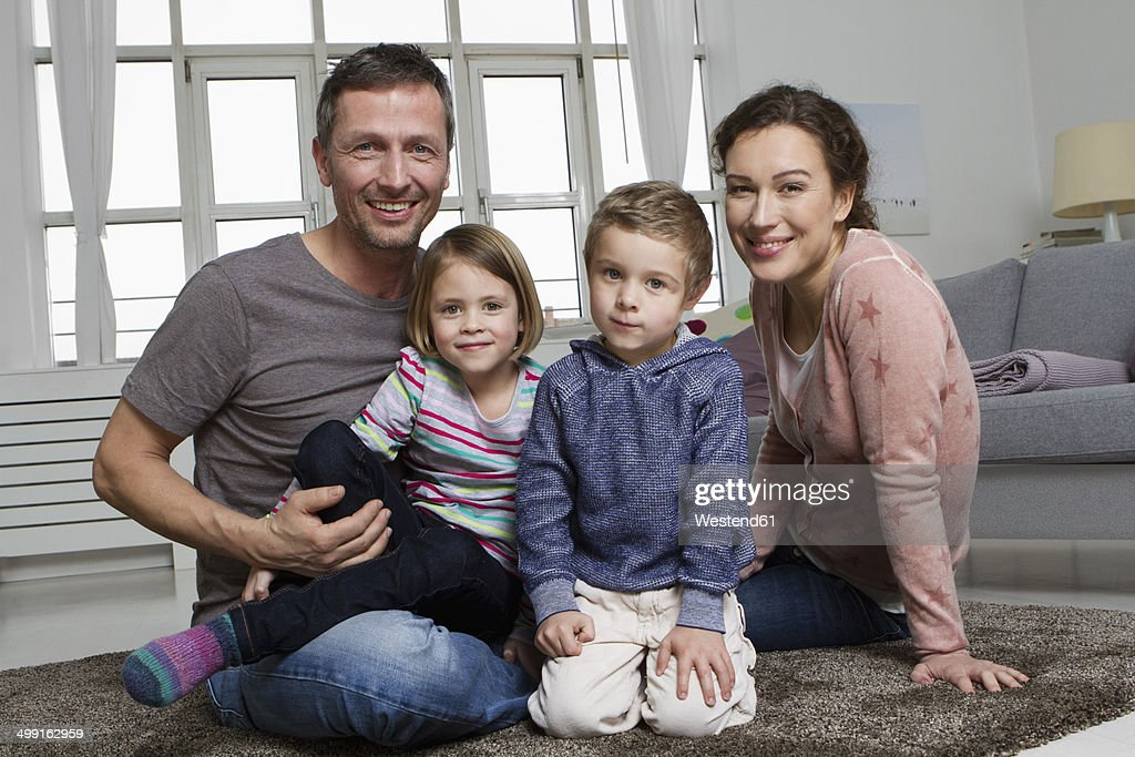 Happy Family Of Four In Living Room High-Res Stock Photo ...