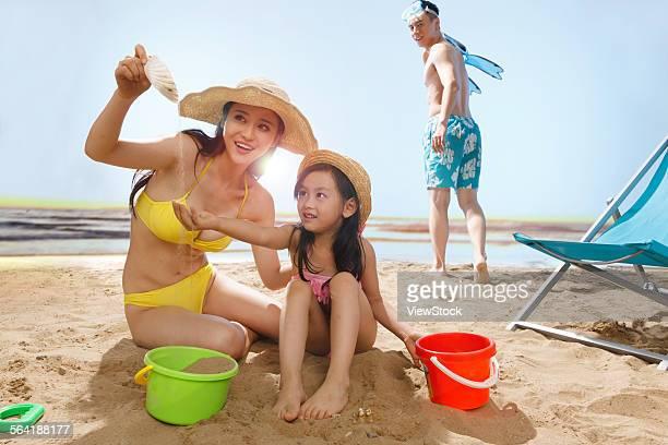 A happy family of four playing on the beach