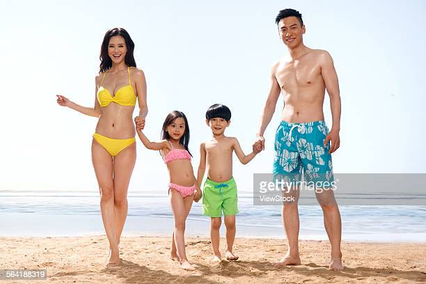 a happy family of four playing on the beach - chinese bikini girls stock pictures, royalty-free photos & images